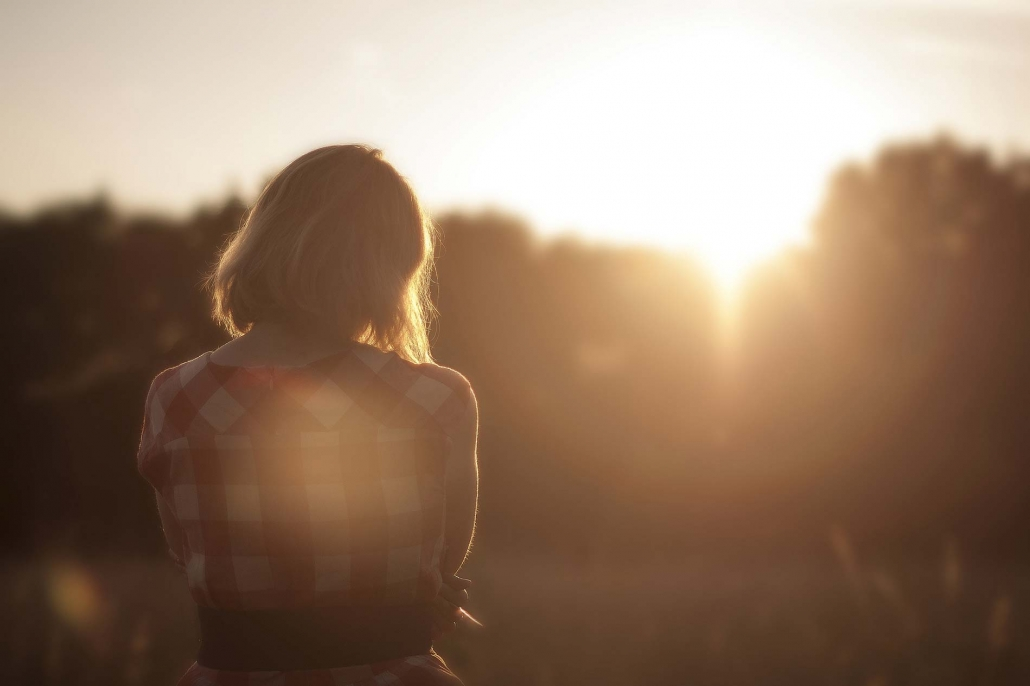 Back of woman looking towards the sun